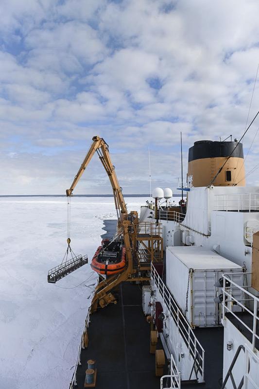 Ein Kranführer senkt die Gangway der Polar Star auf das Eis im McMurdo Sound. Nachdem geeigneten Eis gefunden wurde, konnten Passagier und Crew des Eisbrechers auf dem Eis an Land gehen. (Bild: U.S. Coast Guard)