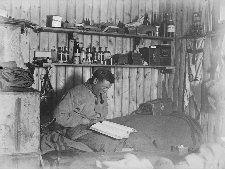 George Murray Levick beim Pfeifenrauchen und Lesen auf seinem Bett in der Hütte von Kap Adare. © P48/14/5 Scott Polar Research Institute, Universität Cambridge