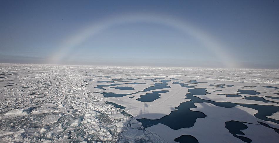 Schmelzwassertümpel am Nordpol im Sommer 2012. Darüber zeigt sich ein schöner Nebelbogen.